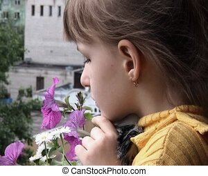 little girl look away from balcony near blossoming petunia