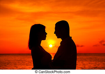 Romantic couple kissing at tropical beach with sunset in the...