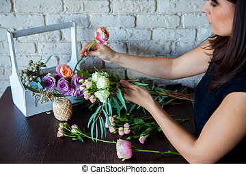 Florist at work. Woman making spring floral decorations