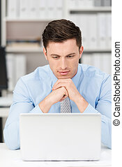 Thoughtful businessman reading his laptop screen -...