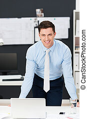 Confident friendly young businessman leaning forwards as he...