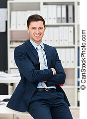 Self-assured successful young businessman sitting on the...