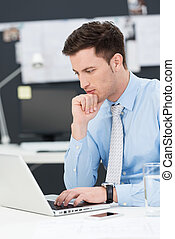 Businessman using a laptop sitting thinking