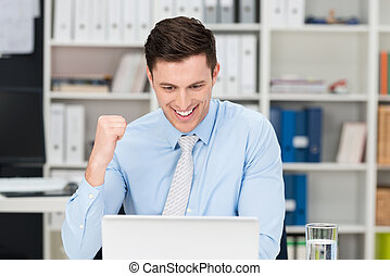 Exultant businessman making a fist and cheering at...