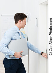 Businessman opening a door as he leaves the office with a...