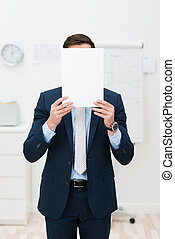 Businessman hiding behind a sheet of paper - Elegant...