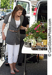 Girl at the market - A young woman buying herbs for her...