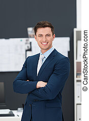 Stylish handsome young businessman standing in the office...