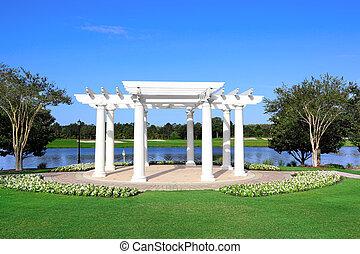 White Gazebo on a Lake Shore with Trees