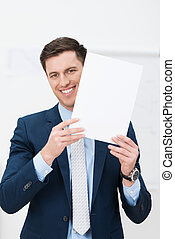 Smiling businessman holding up a page of paper - Smiling...