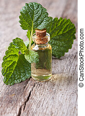 Melissa extract in glass bottle with fresh leaves on the...