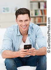 Young man holding his mobile as he relaxes at home