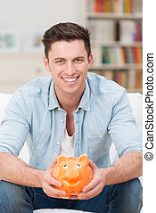 Happy young man holding a piggy bank - Happy attractive...