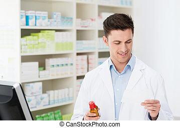 Male pharmacist dispensing prescription drugs holding a...