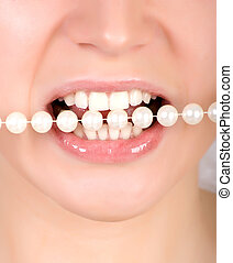 Teeth biting on faux pearls - Woman open mouth and teeth...