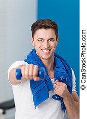 Young man working out with dumbbells - Handsome smiling...