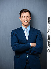 Successful stylish young businessman standing with his arms...