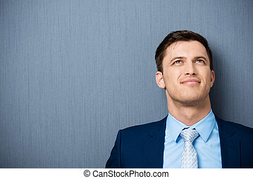 Young businessman deep in thought standing leaning against a...