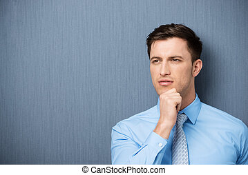 Thoughtful young businessman staring pensively into the...