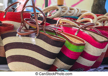 Straw handbags in Mexican market - A row of colorful straw...