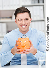 Smiling businessman holding a piggy bank - Successful...