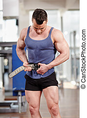 Man fastening belt in the gym - Man fastening his protection...