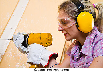 Female carpenter  at work using hand drilling machine