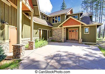 House exterior. Entrance porch - Green and orange siding...