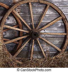 Old wooden wheel on a hay - The old wooden wheel on a hay