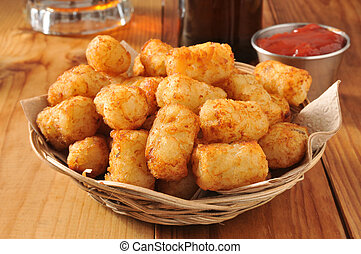 Tater tots - A basket of golden tater tots with beer in the...
