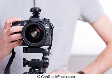 Ready to shoot. Close-up of man holding digital camera while...