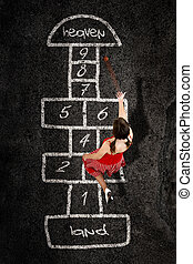 hopscotch - Beautiful young woman playing hopscotch with a...