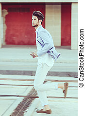 Portrait of a young handsome man, model of fashion, running...