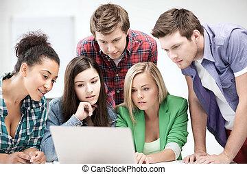 international students looking at laptop at school -...