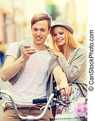 couple with bicycles in the city - summer holidays, apps and...