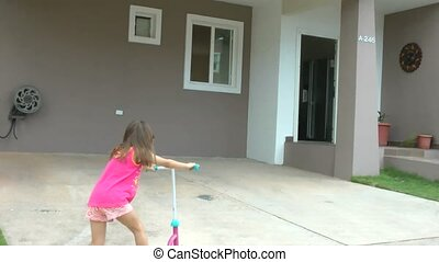 Little girl dropping her scooter in