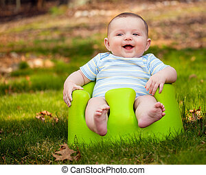 Happy baby using training seat - Happy infant baby boy using...