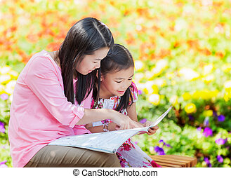 Mon and baby take a home work on the green nature.