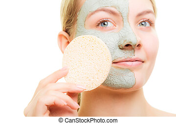 Girl removing facial clay mud mask