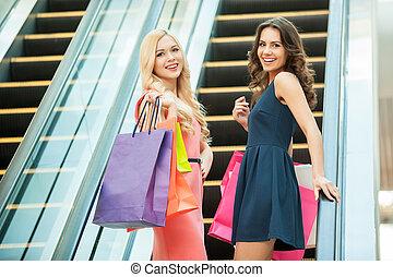 Friends shopping. Two beautiful young women taking escalator in shopping mall