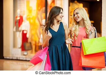Enjoying shopping. Two beautiful young women shopping together and talking
