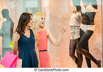 Hey just look at that! Two beautiful young women in dresses holding shopping bags and pointing away