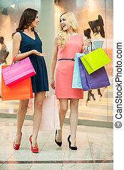 Shopping spree. Beautiful young women shopping in a clothing store