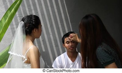 Makeup artist apply makeup to an attractive young groom