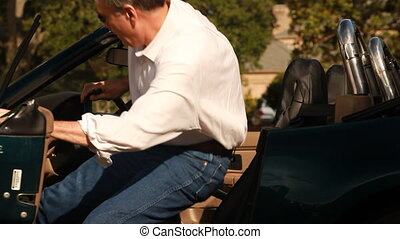 Man Sports Car - A handsome mature fellow gets in his...