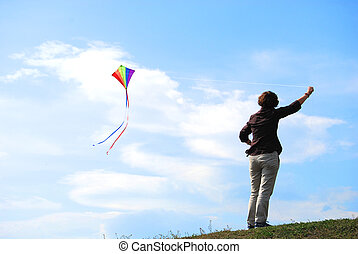 young woman keeps a flying colourful kite
