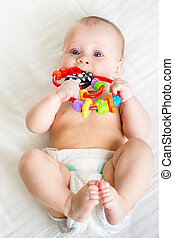 baby girl lying on back weared diaper with toy