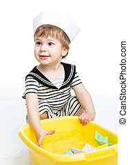 Kid boy with sailor hat  playing with paper boats