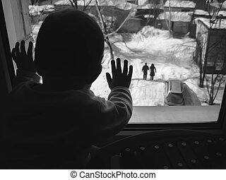 Black and white photo small child looking out the window.