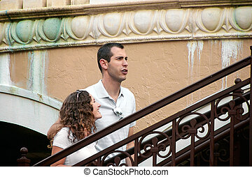 beautiful young couple walking up stairs laughing -...
